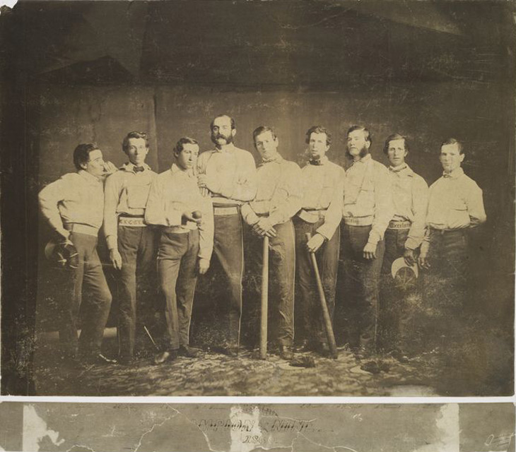 Baseball history photo: Brooklyn Excelsiors 1860 (left to right): Thomas Reynolds, SS; James Whiting, 3B; Jim Creighton (holding ball), P; Henry D. Polhemus, 2B; Aleck T. Pearsall, 1B; Edwin Russell, LF; Joe Leggett, C; Asa Brainard, LF; and George Flanly, CF. When the Civil War began 91 members of the Excelsior Club volunteered, although none of the first nine.  In the winter 1862 Aleck T. Pearsall, who was a physician, volunteered for the Confederates.  He became a Brigade Surgeon in Richmond, Virginia and even attended to some Union prisoners and even members of the Excelsior Club.  When this information reached Brooklyn, the Excelsior Club expelled him.  Click photo to return to previous page.
